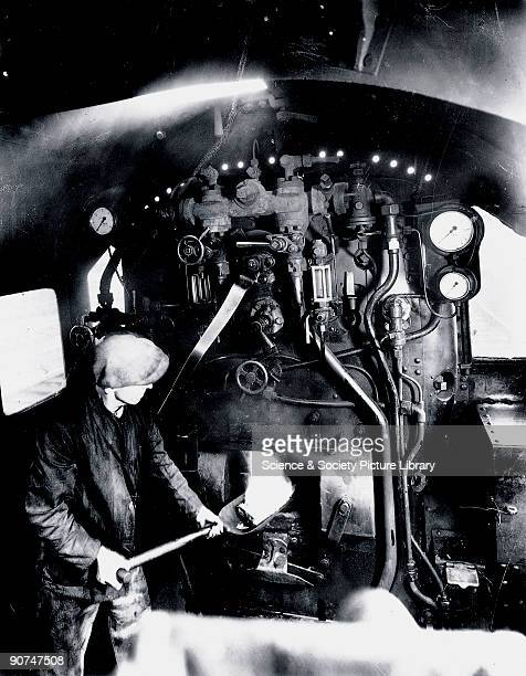 A fireman stokes the furnace in the cab of a London Midland Scottish Railway locomotive