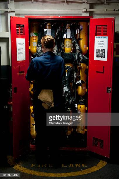 Fireman stows a self-contained breathing apparatus in a locker.
