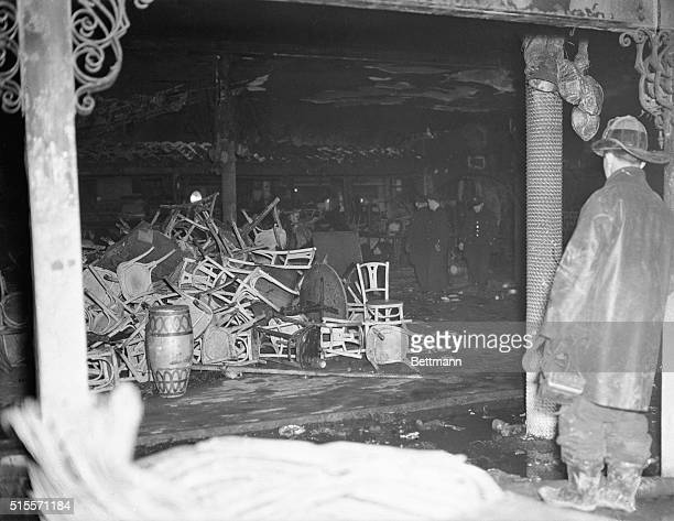 A fireman surveys the ruins of the Cocoanut Grove Night Club destroyed by fire last night He stands beside a pole which was decorated to look like a...