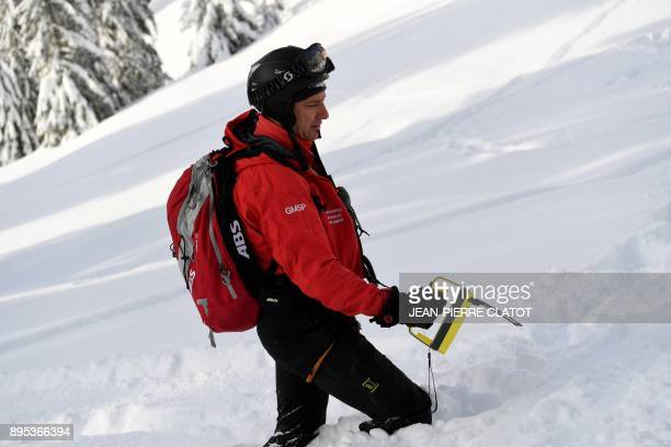 A fireman takes part in a mock rescue operation during an avalanche exercice on December 19 2017 in Les Gets / AFP PHOTO / JEANPIERRE CLATOT