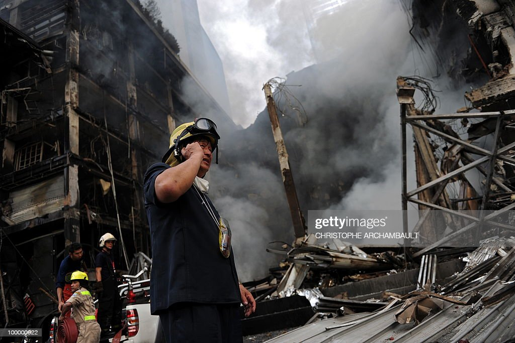 A fireman talks on his mobile phone as his colleagues try to put down a fire at Thailand's biggest shopping mall - Central World - after it was set on fire the day before following an army assault on an anti-government protest site in downtown Bangkok on May 20, 2010. Thailand's biggest shopping mall faces collapse after it was set ablaze by enraged protesters in the wake of an army offensive to shut down an anti-government rally, police said. AFP PHOTO/Christophe ARCHAMBAULT