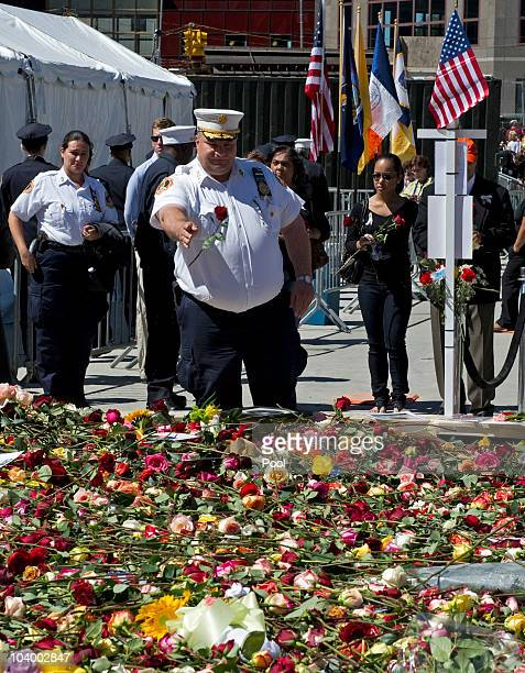 A fireman throws a flowers into the reflecting pool at Ground Zero during the annual 9/11 memorial service September 11 2010 in New York City People...