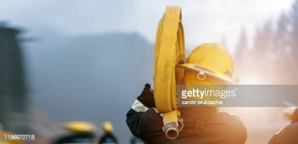 fireman training spray water for helped stop the fire. fire in the industrial factory . rescue ,education ,emergency and teamwork concept . - bombeiro - fotografias e filmes do acervo