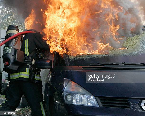 A fireman tries to extinguish a burning car during riots in Nanterre on October 20 a western Paris suburd France Strikes threaten to paralyse...