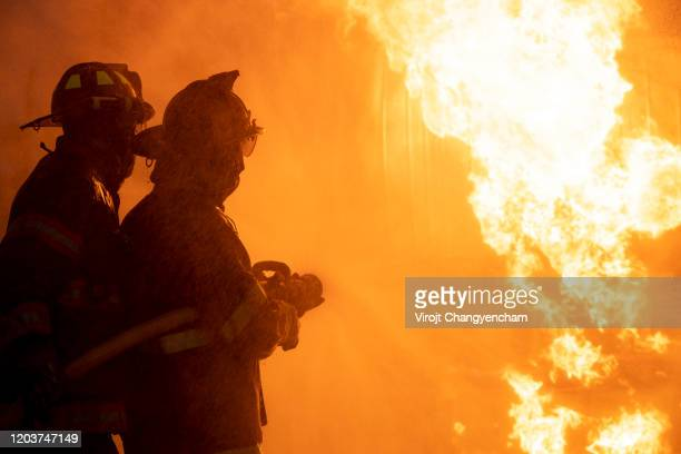 fireman using extinguisher and water from hose for fire fighting at firefight training of insurance group. - burning stock pictures, royalty-free photos & images