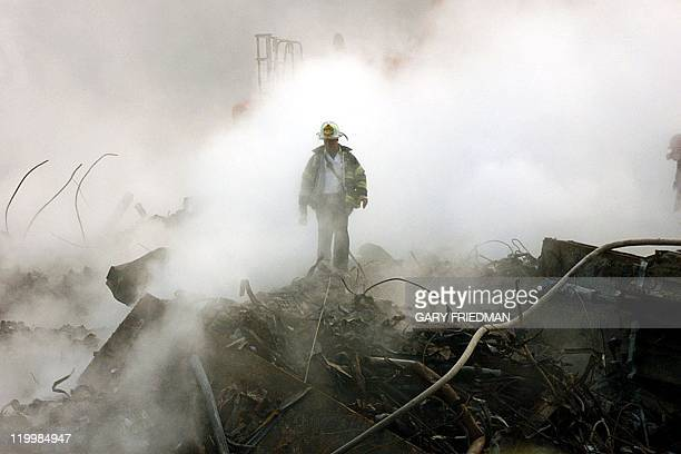 A fireman walks amongst the rubble and the smoldering wreckage of the World Trade Center 11 October 2001 in New York An interfaith ceremony was held...