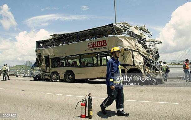 A fireman walks in front of a double decker bus after being lifted back on the road from which it crashed through a highway barrier and fell 50...