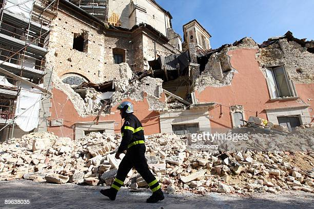 Fireman walks past a government building destroyed in an April earthquake in L'Aquila, Italy, on Wednesday, July 8, 2009. Group of Eight leaders said...