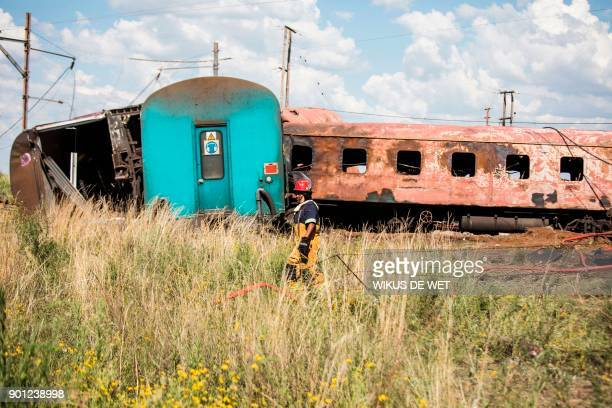 A fireman walks past derailed and burnt train carriages after an accident near Kroonstad in the Free State Province some 110kms southwest of...
