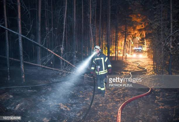 Fireman walks through a burned forest on August 24, 2018 in Klausdorf, northeastern Germany, as a forest fire raging 50 kilometres southwest of...
