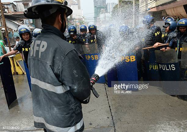 Fireman washes anti-riot policemen with a hose after informal settlers threw pig and human faeces at them during protests against the demolition by...