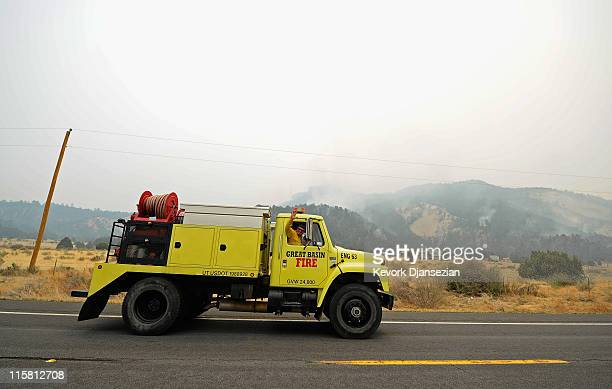 A fireman waves from his truck as he makes his way to the Wallow Fire burning in the hills along US Highway 191 on June 10 in Nutrioso Arizona The...