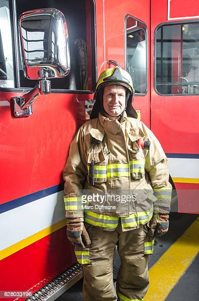 fireman wearing full protection suits besides his truck - fire protection suit - fotografias e filmes do acervo
