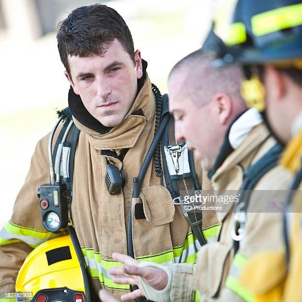 Feuerwehrmann mit Ausrüstung auf anderen Menschen reden hören.