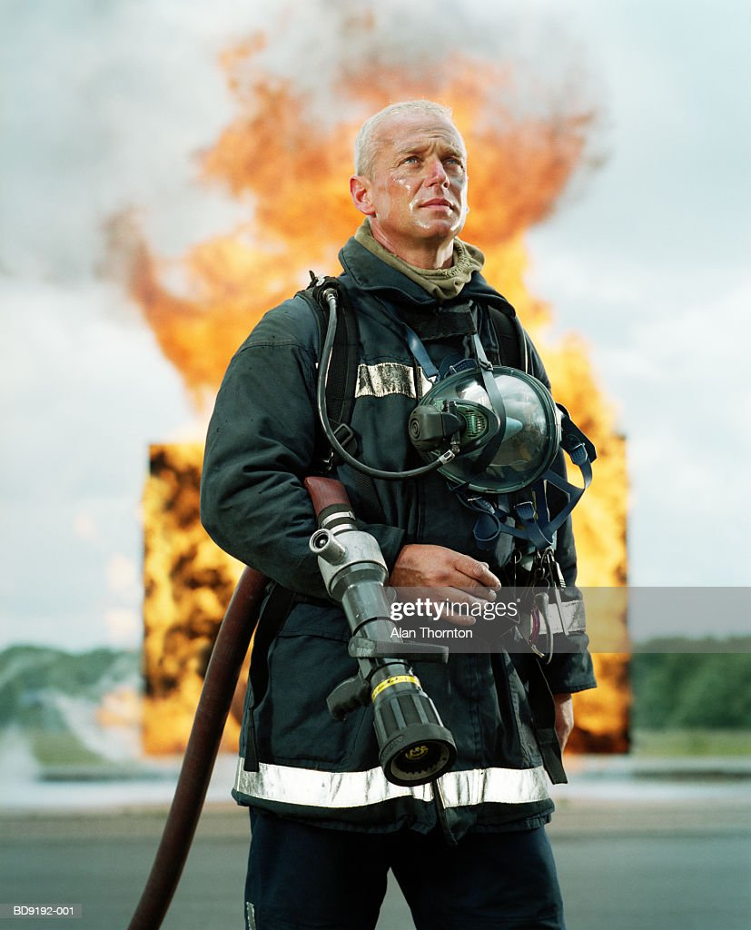 Fireman with hose in front of firewall : Foto de stock