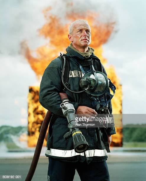 fireman with hose in front of firewall - firefighter stock pictures, royalty-free photos & images