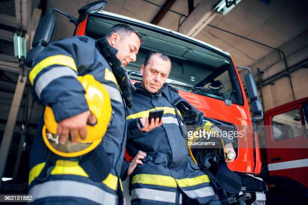 fireman with radio set - firefighter stock pictures, royalty-free photos & images