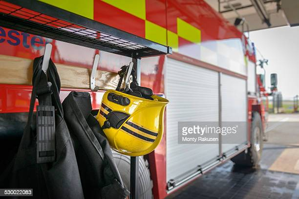 firemans helmet hanging by fire engine in fire station - firefighter stock pictures, royalty-free photos & images