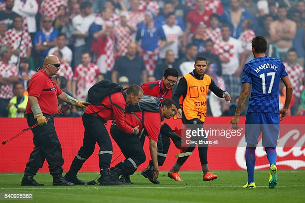 A firemarshall reacts after fireworks are thrown onto the pitch during the UEFA EURO 2016 Group D match between Czech Republic and Croatia at Stade...