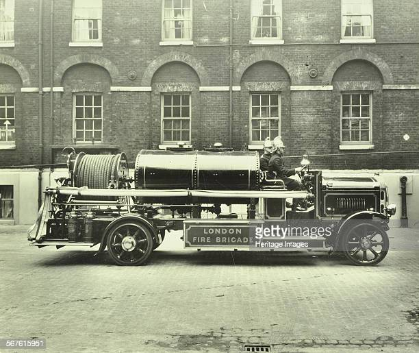 Firemen aboard a foam tender Cannon Street Fire Station London 1929 Firemen with brass helmets sit aboard a vehicle equipped with a hose and large...
