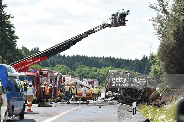 Firemen and forensic experts work at the scene where a tour bus burst into flames following a collision with a trailer truck on the highway A9 near...