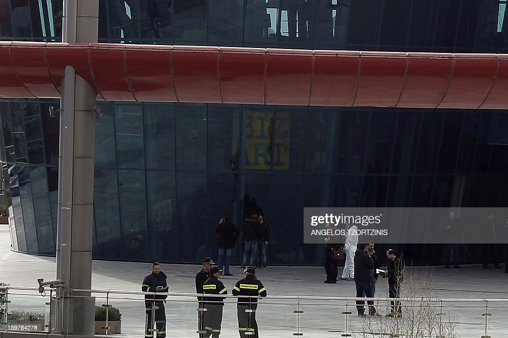 Firemen and police investigators stand outside the multi-storey Athens Mall in a northern suburb of Athens on January 20, 2013 at the site where two security guards were lightly wounded after an explosion. The mall had been evacuated after two warning calls were made to a newspaper and a news website about an hour before the blast. The explosive went off in a garbage can on the first floor of the mall, where shops as well as a branch of the National Bank of Greece are located.