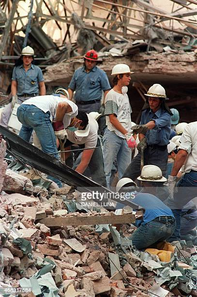 Firemen and rescue workers continue to dig through the ruins of the Israeli Embassy early 18 March 1992 in Buenos Aires after a night of search...