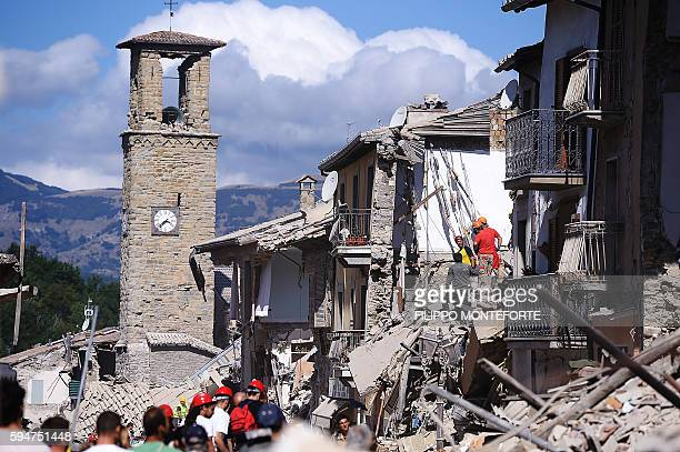 Firemen and rescuers inspect damaged buildings in Amatrice on August 24 2016 after a powerful earthquake rocked central Italy The earthquake left 38...