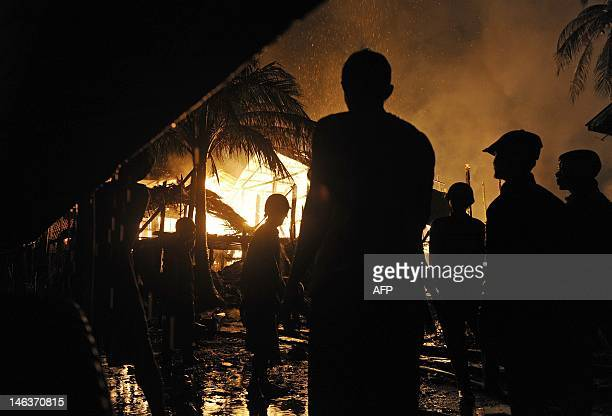 Firemen and residents stand beside burning houses in Sittwe, capital of the western state of Rakhine on June 15, 2012. More than 30,000 people have...