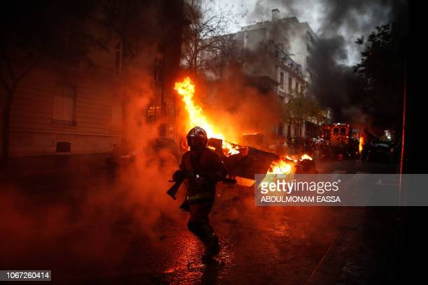 TOPSHOT Firemen are at work to extinguish a burning car on the sideline of a demonstration by Yellow vests protesters against rising oil prices and...