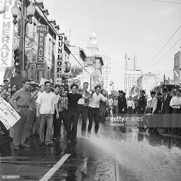 Firemen attempt to break up a protest against desegregation in front of the city hall in New Orleans by aiming a fire hose at the participants
