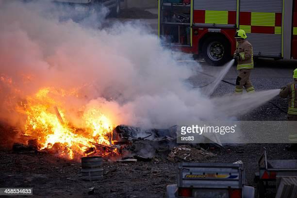 Firemen attending to blazing bonfire