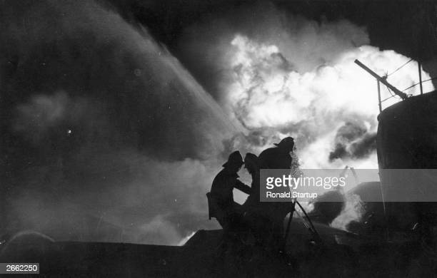 Firemen battling frantically across a chasm of flaming oil to try and isolate a threatened storage tanker in Avonmouth Bristol UK Original...