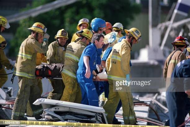 Firemen carry a janitorial worker who was rescued from a collapsed garage at the Northridge Mall after the earthquake on January 17 in Northridge...