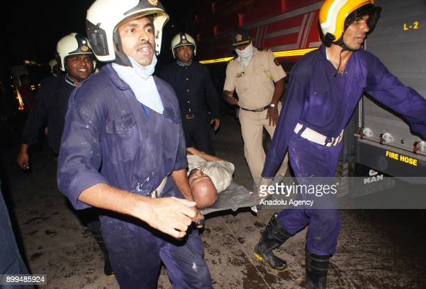 Firemen carry a man with a stretcher from the scene after a fire broke out at a rooftop restaurant in Mumbai India on December 29 2017 At least 15...