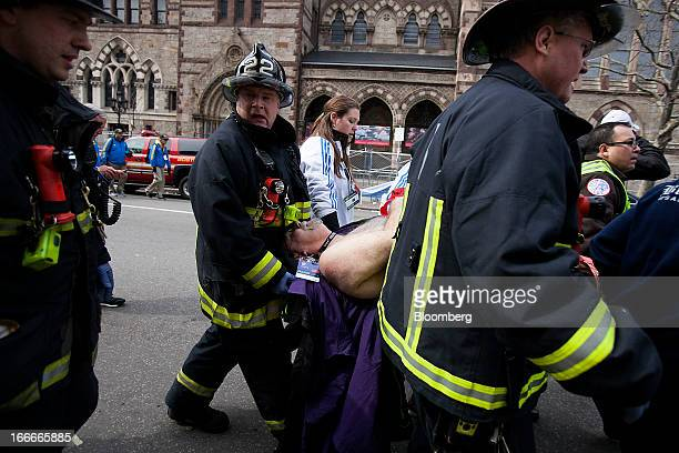 Firemen carry an injured person where two explosions occurred along the final stretch of the Boston Marathon on Boylston Street in Boston...