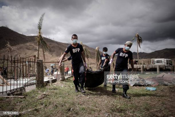 Firemen carry corpses of victims of Typhoon Haiyan during a mass burial on the outskirts of Tacloban, on the eastern island of Leyte on November 14,...