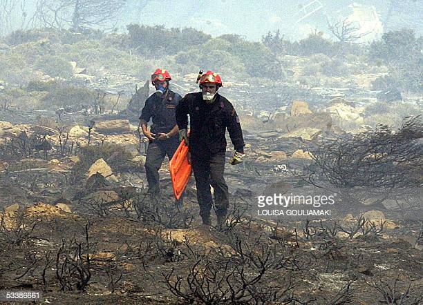 Firemen carry stretchers through the debris of the Cypriot Helios Airways plane carrying 115 passangers and 6 crew , which crashed in the mountains...
