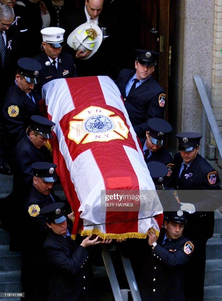 Firemen carry the casket containing the : News Photo