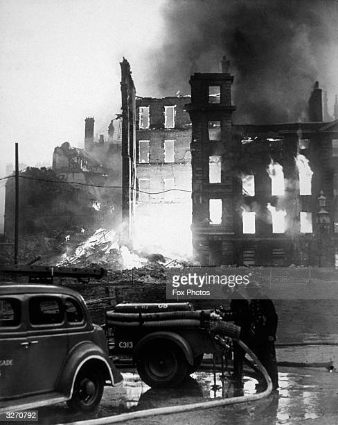 Firemen check their trailer pumps as the historic Temple Buildings burn in the background following a German air raid on London