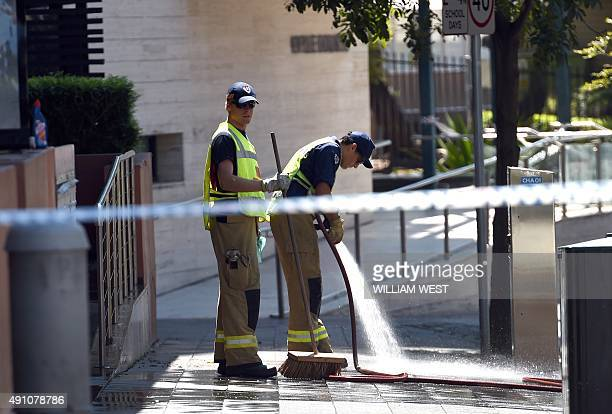 Firemen clean the scene where a 15yearold gunman shot dead a civilian police employee the previous day before being gunned down by police in Sydney...