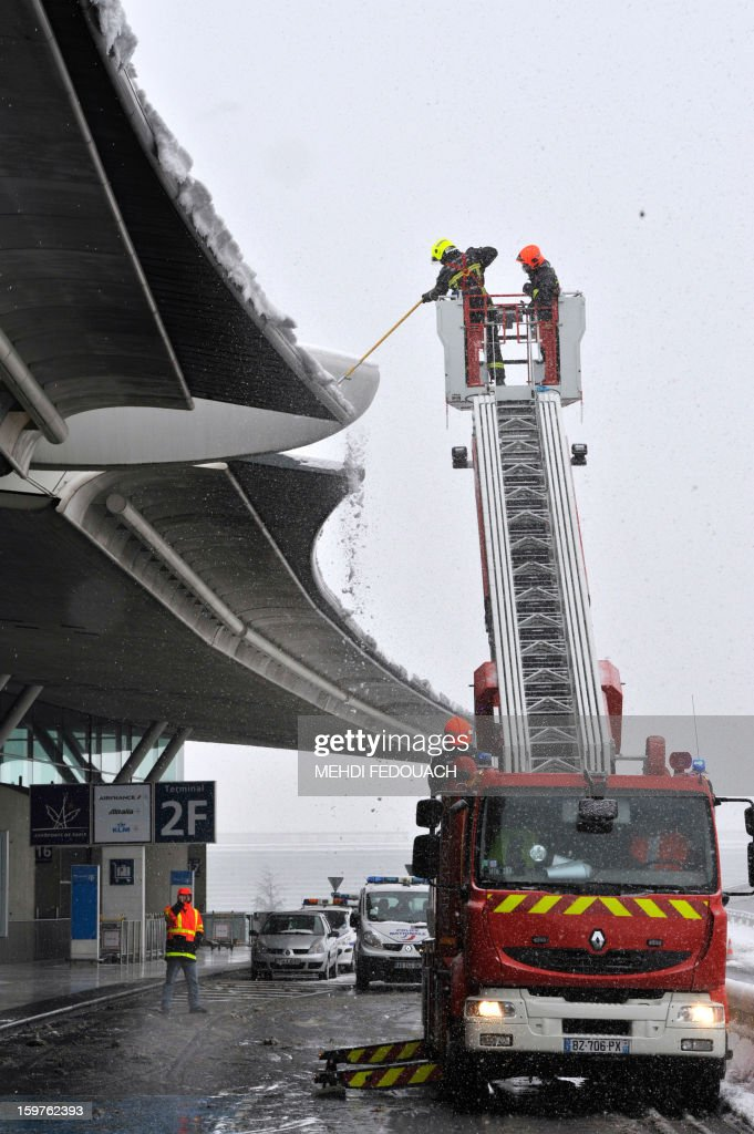Firemen clears the roof of Roissy Charles-de-Gaulle airport terminal 2 from snow, outside Paris, on January 20, 2013. Air France cancelled 40 percent of its short- and medium-haul flights from Paris airports on Sunday as heavy snow disrupted air, road and rail transportation for a second day.