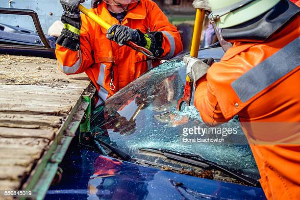 Firemen cutting car window