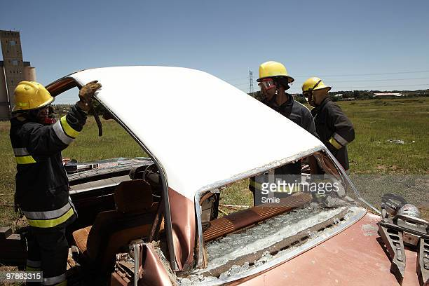 Firemen cutting the roof off a car