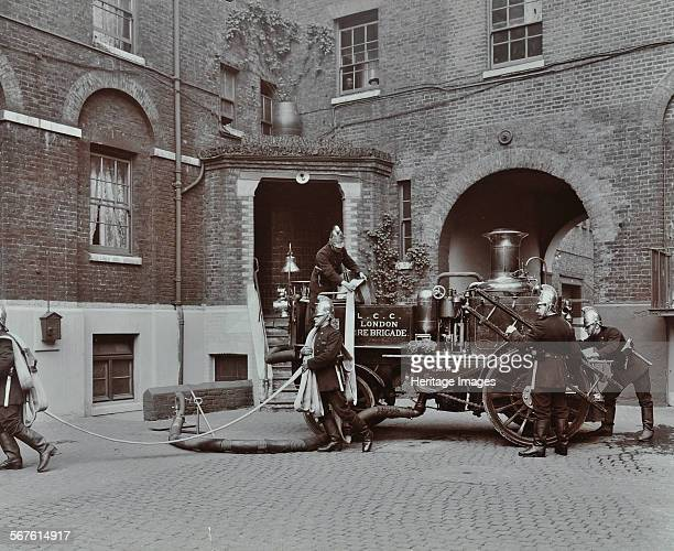 Firemen demonstrating motor steamer hoses London Fire Brigade Headquarters London 1910 Firefighters in brass helmets demonstrate the use of hoses