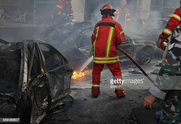 Firemen douse a burning vehicle following a car bomb explosion that rocked central Beirut on December 27 2013 The huge explosion killed Mohamed...