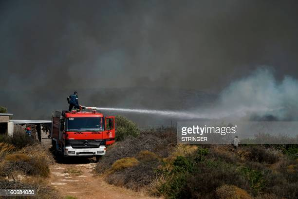 Firemen douse a fire on the island of Elafonissos on the southern edge of Peloponnese Peninsula on August 10 forcing a precautional evacuation of a...