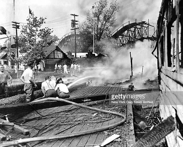 Firemen douse boards to keep flames from spreading in Palisades Amusement Park in Fort Lee NJ where fire destroyed property estimated by the resort's...