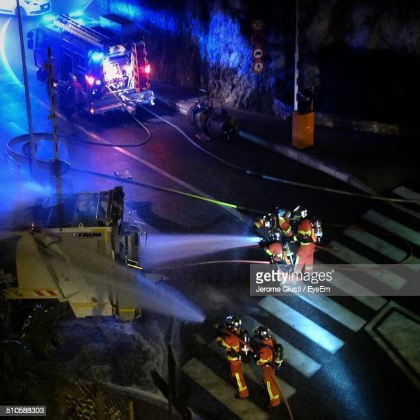 Firemen douse burning bus with water from hose