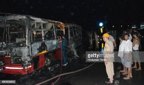 Firemen dousing the fire on bus after the bus collided with a truck near the Bareilly bypass on June 5 2017 in Bareilly India Twentytwo people have...
